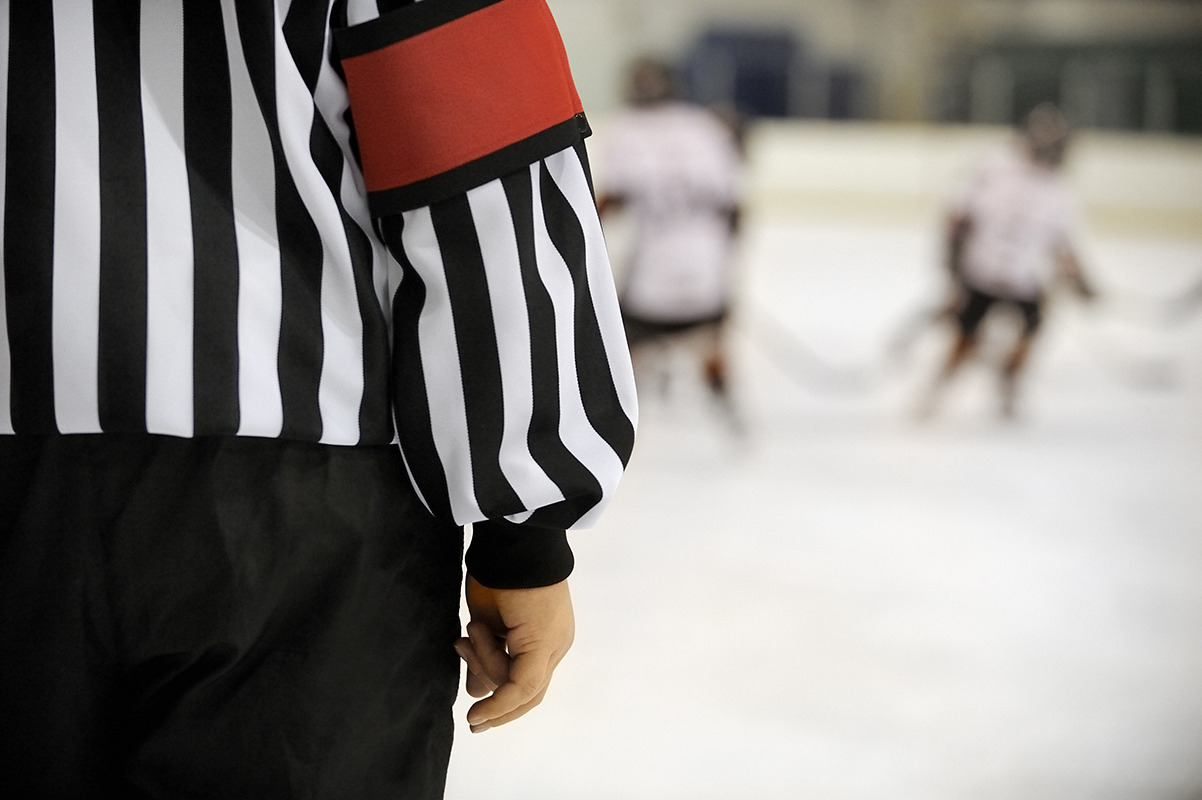 Ice hockey referee in front of players with copy space.Click on an
